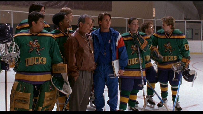Grafika przedstawia scenę z hokejowego filmu Potężne Kaczory.