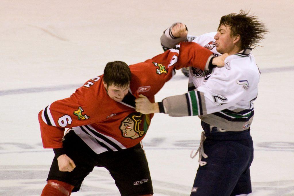 Hokejowe filmy - grafika wyróżniająca. Przedstawia dwóch graczy NHL walczących na pięści.